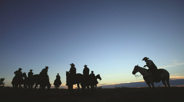Waggoner Ranch cowboys prepare to ride out at dawn.