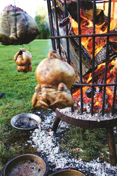 THE HEAT IS ONE. Wood-grilled sumac-rubbed heritage chickens cook to perfection.